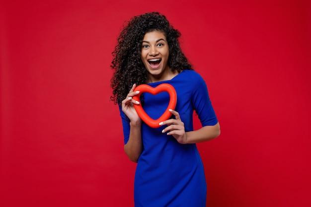 Mulher negra com forma de coração, sorrindo e usando vestido azul na parede vermelha
