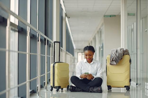 Mulher negra com mala no aeroporto