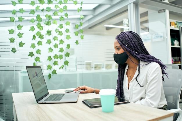 Mulher negra com máscara trabalhando no escritório