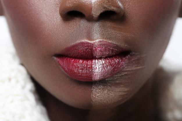 Mulher negra com metade do rosto na maquiagem, conceito de beleza