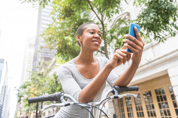 Mulher negra com moto escrevendo no telefone