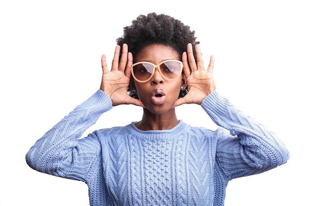 Mulher negra com óculos gritando com as mãos perto do rosto