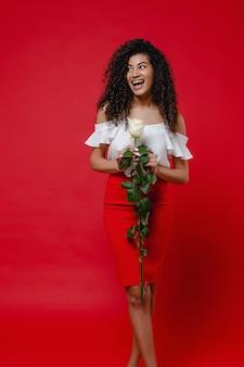 Mulher negra com rosa branca, sorrindo na parede vermelha
