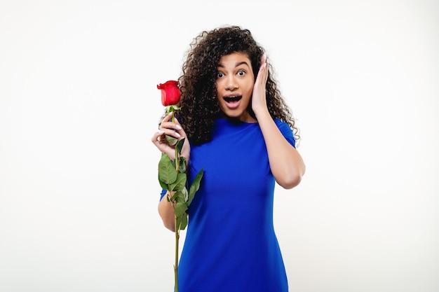 Mulher negra com rosa vermelha, vestido azul isolado
