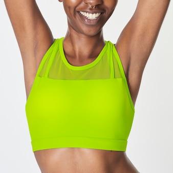 Mulher negra com sutiã esportivo amarelo neon