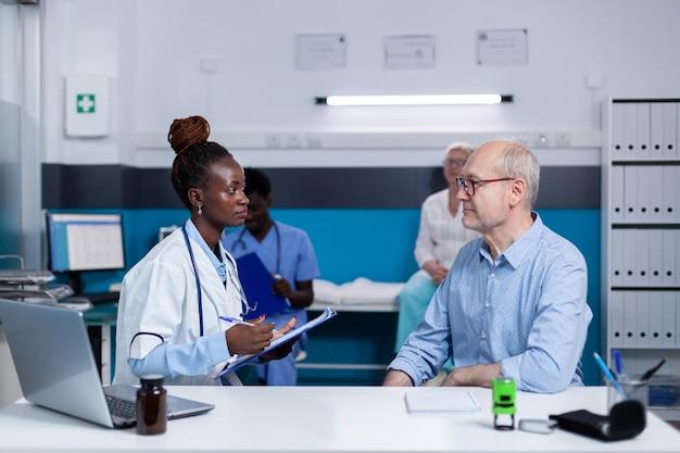 Mulher negra com trabalho médico, consultando paciente idoso