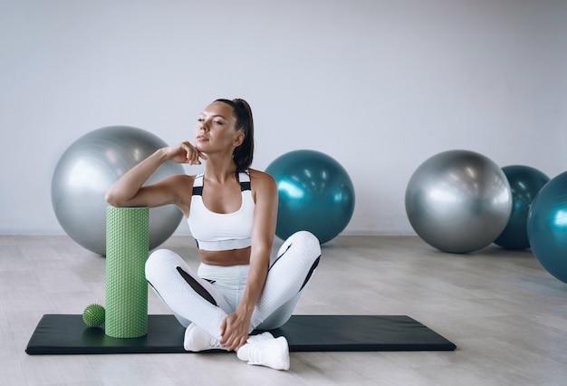Mulher negra com um agasalho de treino branco na academia com fit foam roller