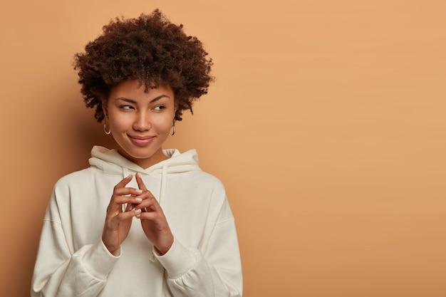 Mulher negra complicada tem um grande plano maligno, mantém as mãos juntas e olha com intenção de fazer algo, planeja fazer coisas interessantes