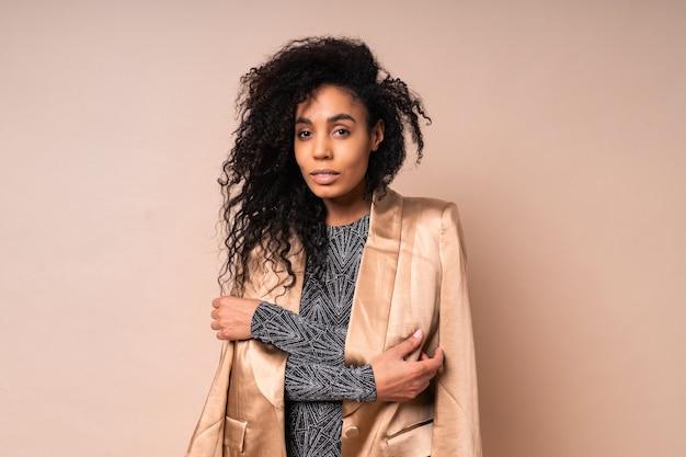 Mulher negra confiante em jaqueta de seda dourada e vestido brilhante com corpo bronzeado perfeito posando.