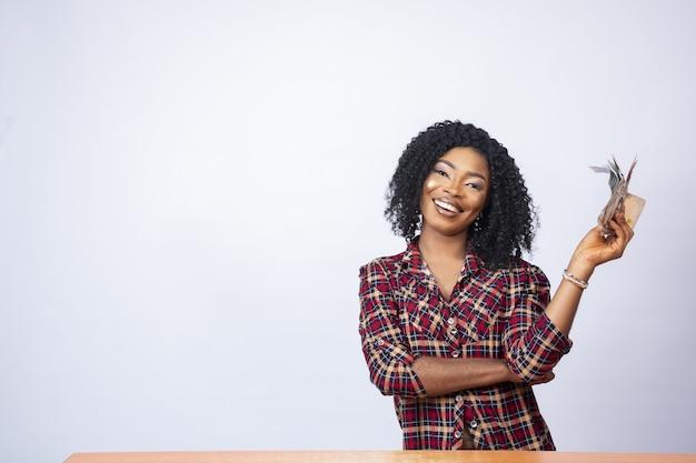 Mulher negra confiante sentada e exibindo um maço de dinheiro