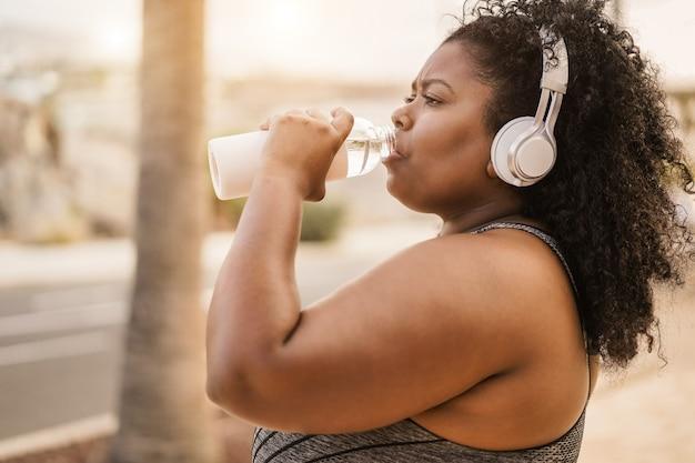 Mulher negra curvilínea bebendo água após rotina de corrida ao ar livre no parque da cidade - foco no rosto