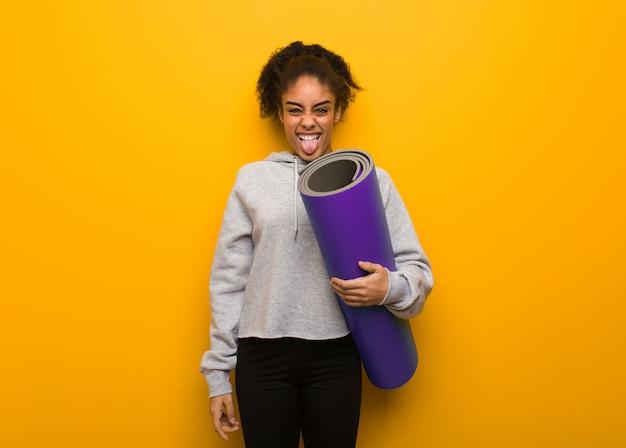Mulher negra da aptidão nova funnny e língua mostrando amigável. segurando um tapete.