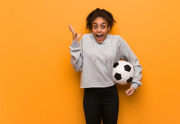 Mulher negra da aptidão nova que comemora uma vitória ou um sucesso. segurando uma bola de futebol.