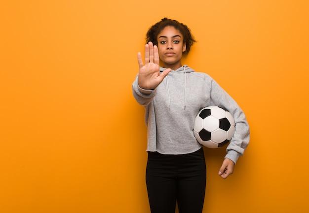 Mulher negra de aptidão jovem, colocando a mão na frente. segurando uma bola de futebol.