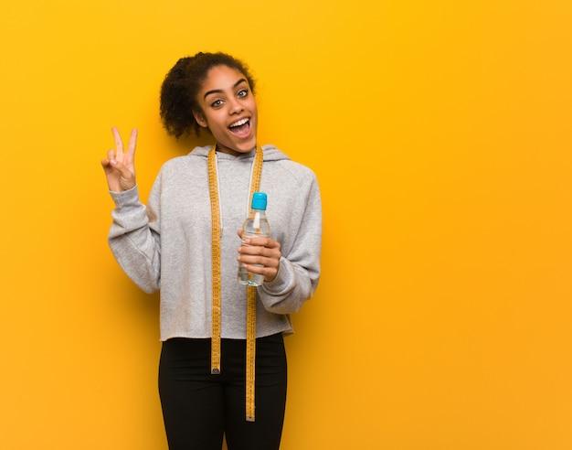 Mulher negra de aptidão jovem, fazendo um gesto de vitória. segurando uma garrafa de água.