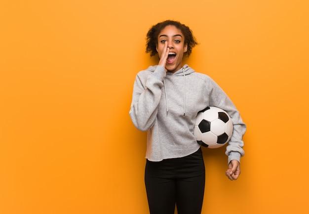 Mulher negra de aptidão jovem gritando algo feliz para a frente. segurando uma bola de futebol.