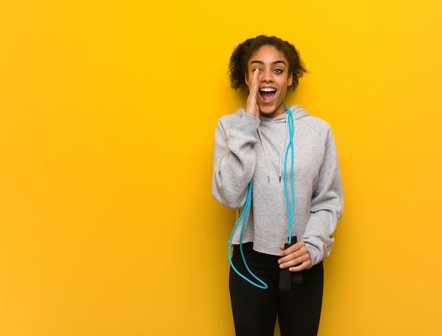 Mulher negra de aptidão jovem gritando algo feliz para a frente