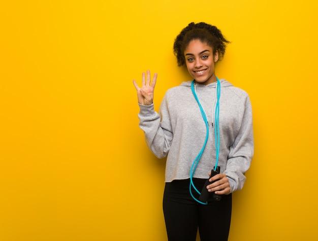 Mulher negra de aptidão jovem mostrando o número quatro. segurando uma corda de pular.