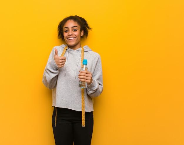 Mulher negra de aptidão jovem sorrindo e levantando o polegar. segurando uma garrafa de água.