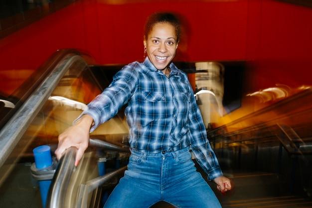 Mulher negra de meia-idade rindo em uma estação de metrô. fotografia com efeito de movimento. conceito de vida noturna e psicologia