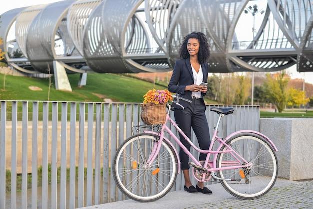 Mulher negra de negócios aguardando sua bicicleta vintage, falando no telefone celular