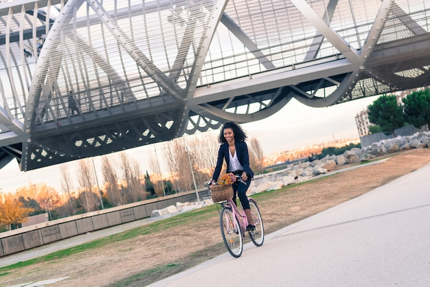 Mulher negra de negócios andando de bicicleta vintage na cidade
