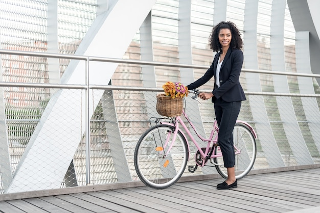 Mulher negra de negócios com bicicleta vintage em uma ponte