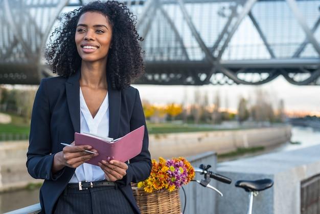 Mulher negra de negócios com bicicleta vintage pelo rio, olhando para a agenda dela