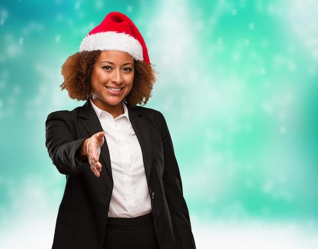 Mulher negra de negócios jovem usando um chapéu de papai noel chirstmas chegando para cumprimentar alguém