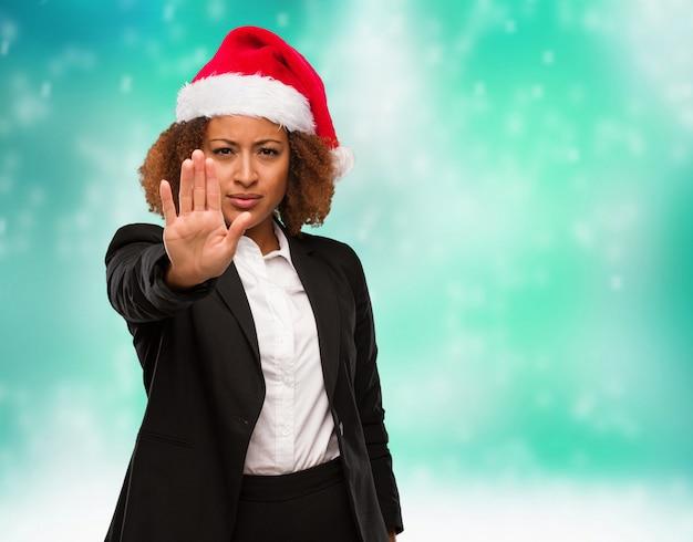 Mulher negra de negócios jovem usando um chapéu de papai noel chirstmas colocando a mão na frente