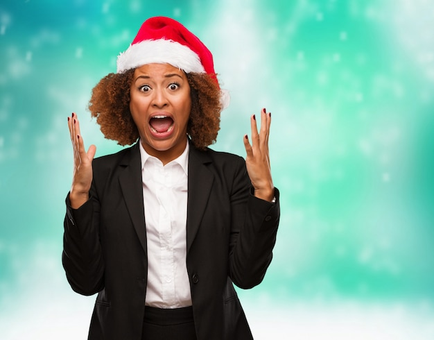 Mulher negra de negócios jovem usando um chapéu de papai noel chirstmas comemorando uma vitória ou sucesso