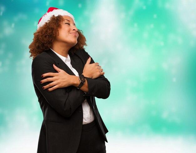 Mulher negra de negócios jovem usando um chapéu de papai noel chirstmas dando um abraço