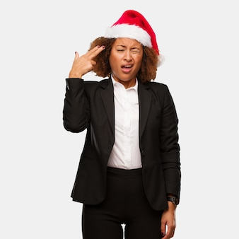 Mulher negra de negócios jovem usando um chapéu de papai noel chirstmas fazendo um gesto de suicídio