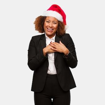 Mulher negra de negócios jovem usando um chapéu de papai noel chirstmas fazendo um gesto romântico
