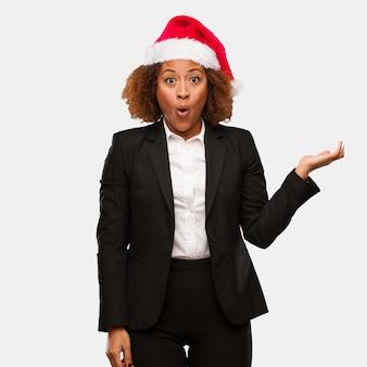 Mulher negra de negócios jovem usando um chapéu de papai noel chirstmas segurando algo na palma da mão