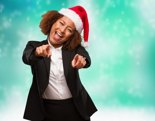 Mulher negra de negócios jovem vestindo um chapéu de papai noel alegre e sorridente