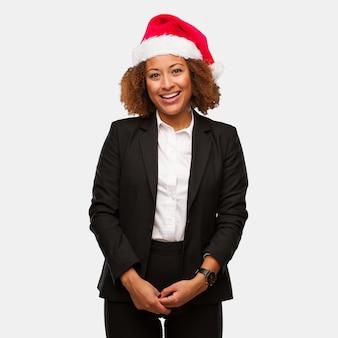 Mulher negra de negócios jovem vestindo um chapéu de papai noel chirstmas alegre com um grande sorriso