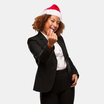 Mulher negra de negócios jovem vestindo um chapéu de papai noel chirstmas convidando para vir