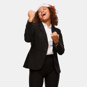 Mulher negra de negócios jovem vestindo um chapéu de papai noel chirstmas que não se rende