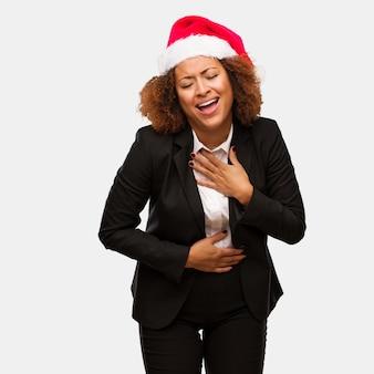 Mulher negra de negócios jovem vestindo um chapéu de papai noel chirstmas rindo e se divertindo