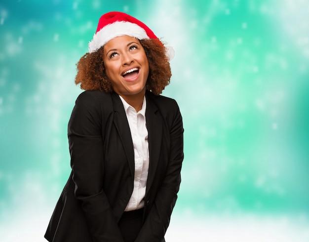 Mulher negra de negócios jovem vestindo um chapéu de papai noel chirstmas sonhando em alcançar objetivos e finalidades