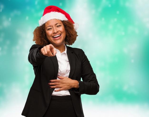 Mulher negra de negócios jovem vestindo um chapéu de papai noel chirstmas sonhos de alcançar objetivos e propósitos