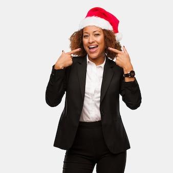 Mulher negra de negócios jovem vestindo um chirstmas santa chapéu sorrisos, apontando a boca