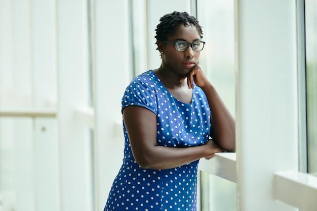 Mulher negra de óculos e vestido de bolinhas em pé pela janela com a cabeça descansando na mão