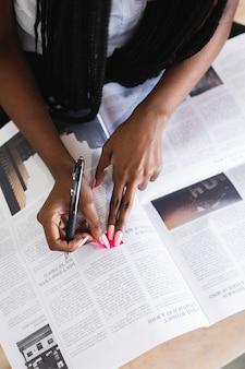 Mulher negra destacando matéria de jornal