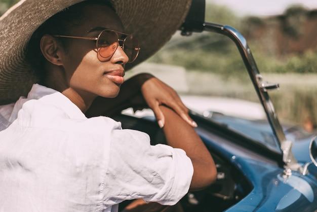 Mulher negra, dirigindo um carro conversível antigo