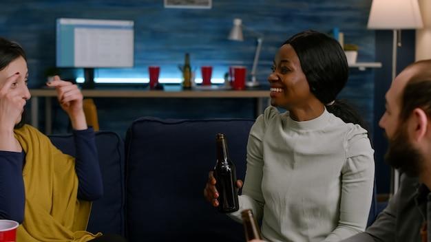 Mulher negra discutindo com seus amigos enquanto segura a garrafa de cerveja relaxante no sofá à noite na sala de estar. grupo de pessoas mestiças curtindo o tempo juntos