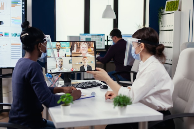 Mulher negra e colega de trabalho, tendo uma videochamada financeira com empresários. novo escritório comercial normal. equipe multiétnica trabalhando respeitando a distância social durante a pandemia global de coronavírus.