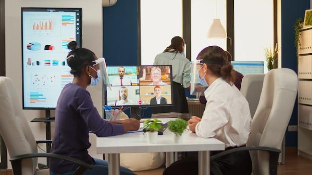 Mulher negra e empresário co-empresário usando máscaras protetoras, falando com colegas remotamente na videochamada. novo escritório normal de negócios equipe multiétnica trabalhando respeitando a distância social.