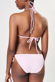 Mulher negra em biquíni rosa claro de duas peças